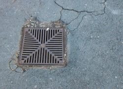 A square metal water drain grid set in cracked tarmac