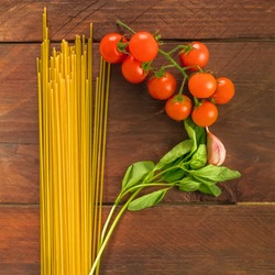 A square overhead photo of a letter P for pasta, formed by spaghetti, cherry tomatoes, a garlic clove, and a sprig of basil leaves, on a dark wooden background texture with copy space