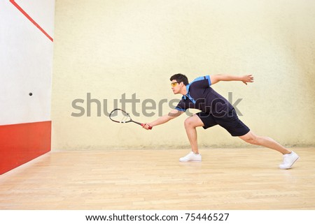 A squash player hiting a ball in a squash court ストックフォト ©