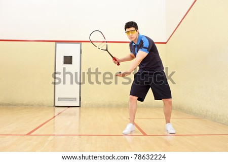 A squash player serving a ball in a squash court