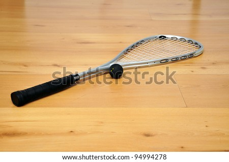 a squash racket and ball on the floor
