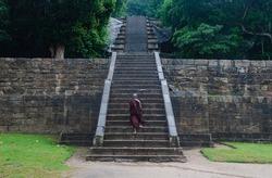 A Sri Lankan Buddhist Monk Climbling the stairways on the way to Yapahuwa Rock fortress located between Kurunegala and Dambadeniya