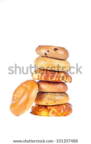 A stack of assorted, fresh, flavorful bagels on a white background. Bagels consist of onion, cheese, sesame, plain and blueberry.