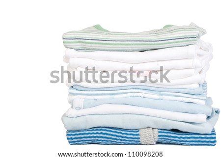 a stack of baby clothes on a white background with copy space