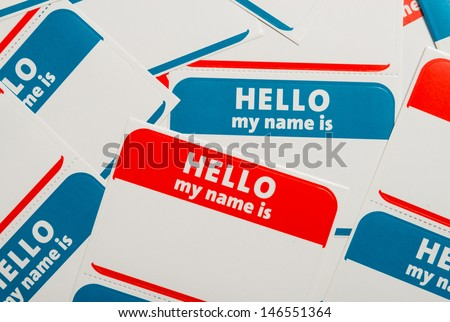 "A stack of blue and red ""Hello, my name is"" name tags or badges"
