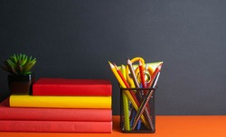 A stack of books, a green flower, and a glass of pencils stand on an orange background.