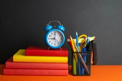 A stack of books, a green flower, blue clock and a glass of pencils stand on an orange background.