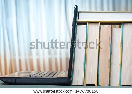 A stack of books and textbooks are leaning on a laptop. Educational concept.