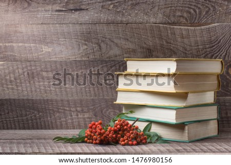 A stack of books and textbooks on a wooden table, red Rowan berries.