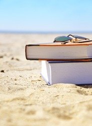 A stack of books in on the ocean sand with beach sunglasses. The water is in the background. Use it for a vacation or travel concept.