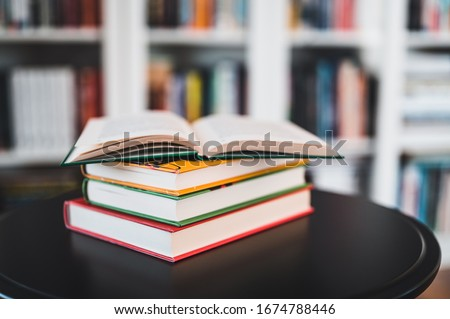A stack of books on a black table. Library in the background. Stack of books close up.