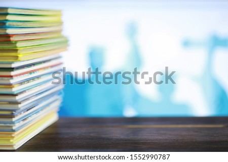 A stack of books. Textbooks on the table. Tutorials are on desk.