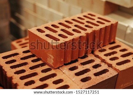 A stack of bricks for construction, hollow brick. Material for construction and repair. Clay brick, brick texture, preparation for the construction process