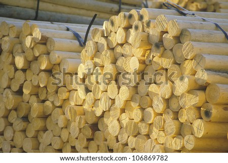 A stack of bundled logs shaped into fence posts - stock photo