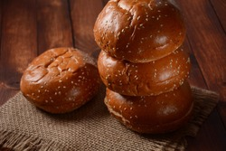 A stack of burger buns. Round bread on wooden board