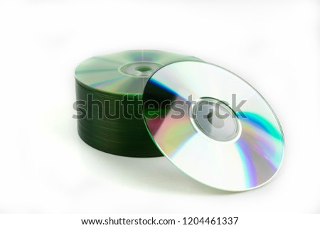 A stack of CD or DVD storage media discs neatly stacked with one disc offset and leaning on the others while creating a rainbow of colors from the prismatic effect of the shiny recording surface.