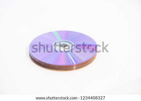 A stack of CDs/DVDs - Blank recordable DVDs (DVD-R) purple discs on white background #1234408327