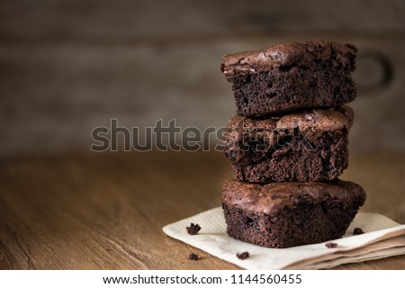 A stack of chocolate brownies on wooden background, homemade bakery and dessert #1144560455