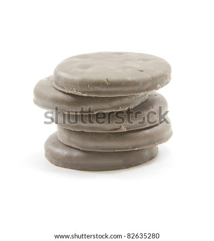 A stack of chocolate mint thin round cookies piled high.