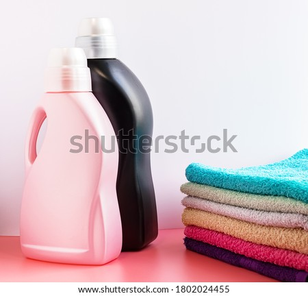 A stack of clean towels and plastic bottles of detergent and fabric softener on the table. Space for text Laundry, household chores and responsibilities. Laundry day Foto stock ©