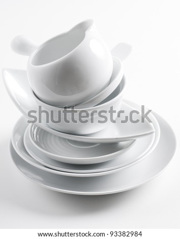 A stack of clean white different dishes on a white background
