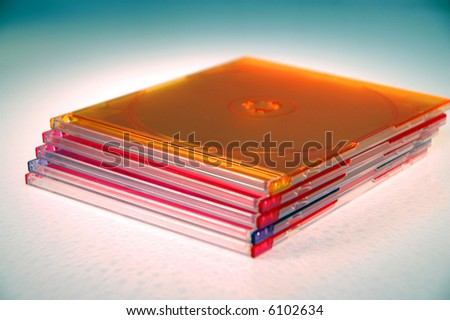 A stack of colored  CD-ROM cases against a white background.