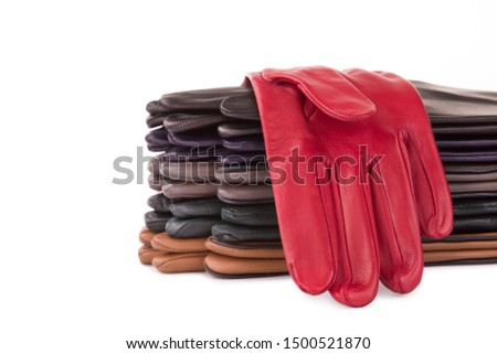 A stack of colored leather gloves on a white background. Red gloves. Colored leather gloves.