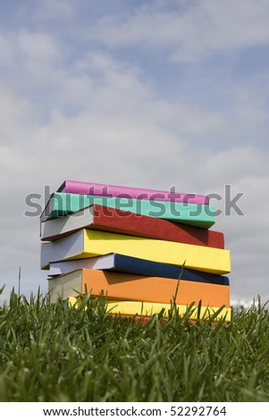 A stack of colorful books on the grass