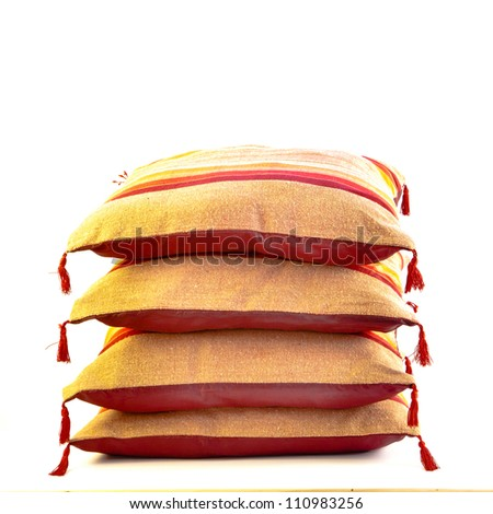 A stack of colorful moroccan cushions on a white background