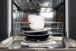 a stack of dirty dishes is on the door of the dishwasher