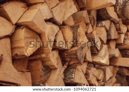 A stack of dry firewood, prepared for winter. Material for heating the house. Ecological natural fuel. Firewood texture for the background.  #1094062721