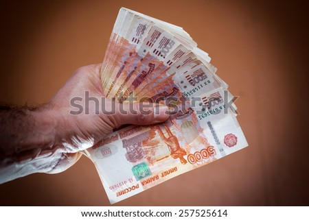 A stack of five thousand bills in the men\'s hands.