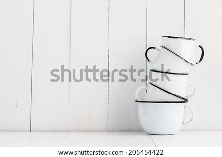 A stack of five white enameled mugs on painted wooden table, kitchen utensils and decor, rustic vintage kitchen background