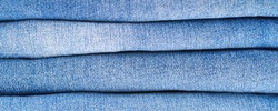 A stack of folded blue jeans close-up denim texture banner background, a variety of comfortable casual pants and clothing. Natural organic cotton fabric wear backdrop.
