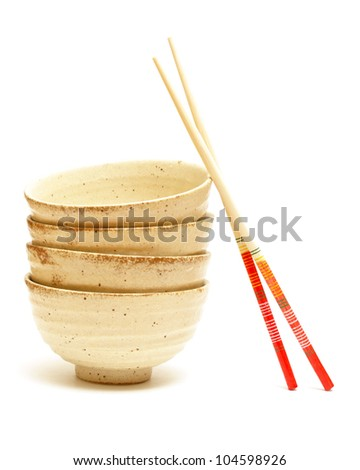 A stack of four rice bowls with chopsticks.