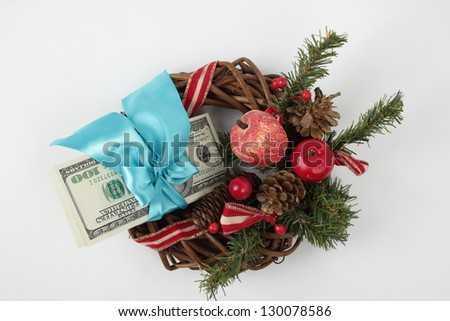 A stack of hundred-dollar bills in a blue gift ribbon and Christmas decorations