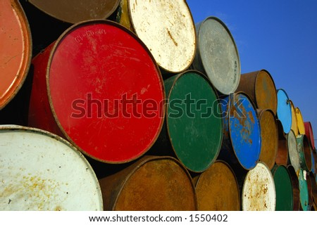 A stack of multi-coloured oil barrels, towering in to the clear blue sky. Space for text in the sky.