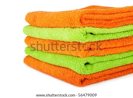 A stack of multicolored orange and green towels on the white background