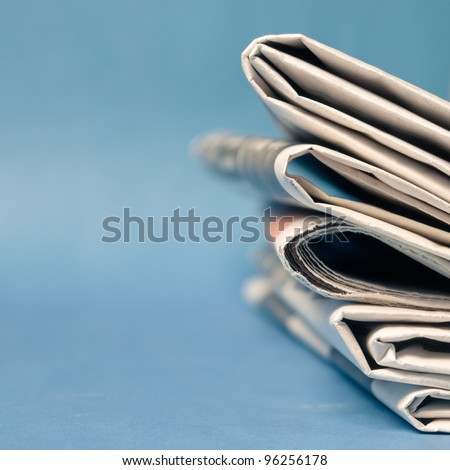 A stack of newspaper on blue background