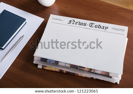 "A stack of newspapers with headline ""News Today"" and blank space for information lying on the office desktop."