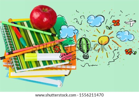 A stack of notebooks and textbooks with pens and a red Apple with a dreamy illustration
