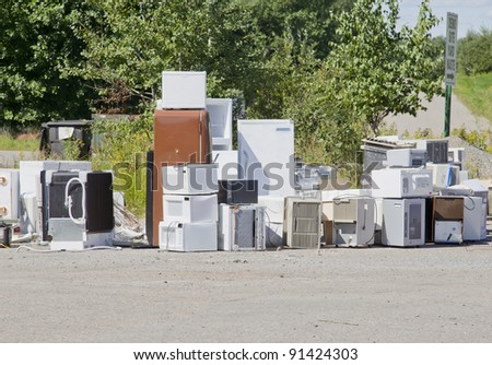 A stack of old appliances such as refrigerators, freezers, and air conditioners stacked up in a pile at a recycling garbage dump.