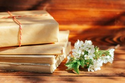 a stack of old books on a wooden background with a sprig of a flowering tree. the concept of memorabilia and historical notes