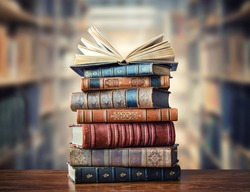 A stack of old books on table against background of bookshelf in library. Ancient books as a symbol of knowledge, history, memory and information.