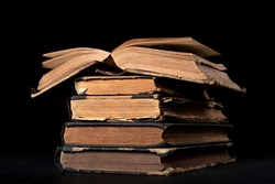 A stack of old books on the desk. Old extensive literary publications. Dark background.
