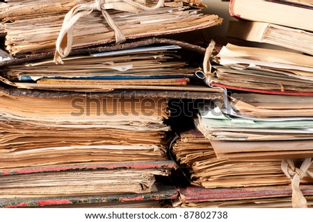 A stack of old files yellowing in an archive