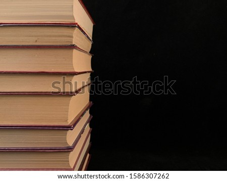 A stack of old hardcover textbooks, on a black background. Thick Books are stacked in a row. Concept: education, self-improvement, love of learning.
