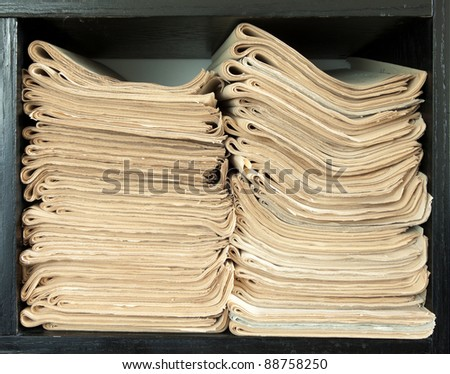 A stack of old newspapers, old, fat yellow.