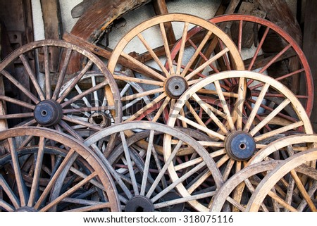 A stack of old rusty wooden wheels against a wall. #318075116