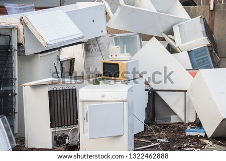A stack of old white electrical household appliances waste such as a fridge or microwave, ecologically disposed of in a landfill (dump, collection yard). of hazardous waste. #1322462888